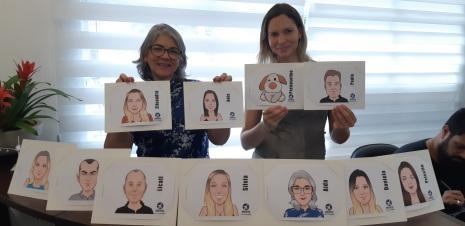 Aida Villa e Daniela Cerqueira, com as caricaturas dos presentes à festa, feitas pela Officina do Risco