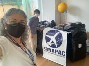 Aida Villa, gerente administrativo da ABRAPAC, na entrega da doação à Casa do Todos